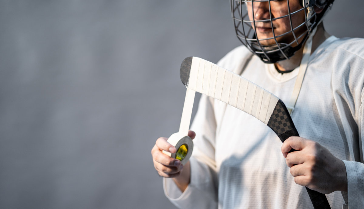 Player using hockey tape to tape his stick